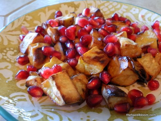 Pomegranate seeds over roasted sweet potatoes